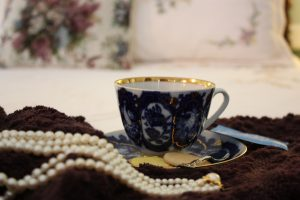 A beautiful blue and gold cup o Bloomsbury coffee and white pearls rest on the bed at Bloomsbury