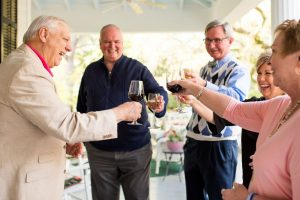 Owner of Bloomsbury Inn welcomes guests to the front porch for a glass of wine.
