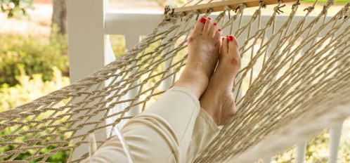 At Bloomsbury Inn, a guest relaxes in the hammock and sips a glass of red wine.