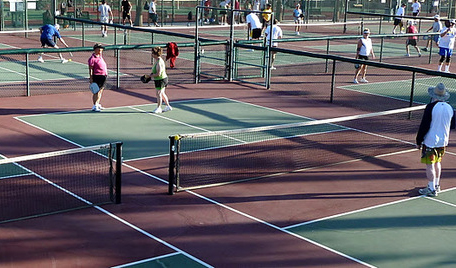 A group of people playing pickleball.