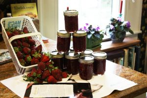 Jars of strawberry jam stacked beside fresh strawberries. The forefront book contains great recipes for canning competition.