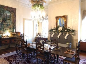 A fuller view of the dining room shows the tree, mantel and chandelier decked in gold.