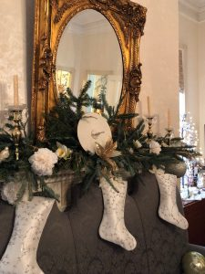 The mantel in the dining room is dressed in gold with 3 cream/gold stockings all hung with care.