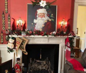 The mantel hosts a large picture Santa and the family stockings.