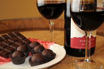 A small tray of chocolates with red wine service.