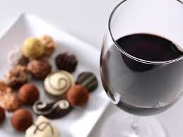 Aa small tray of chocolates pared with a glass of red wine