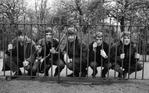 "Members of the band ""The Animals"" peeking through a fence."