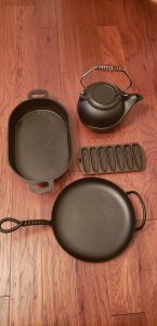 Collection of four pieces of restored cast iron: kettle, roaster, cornbread flat and a wrought iron skillet